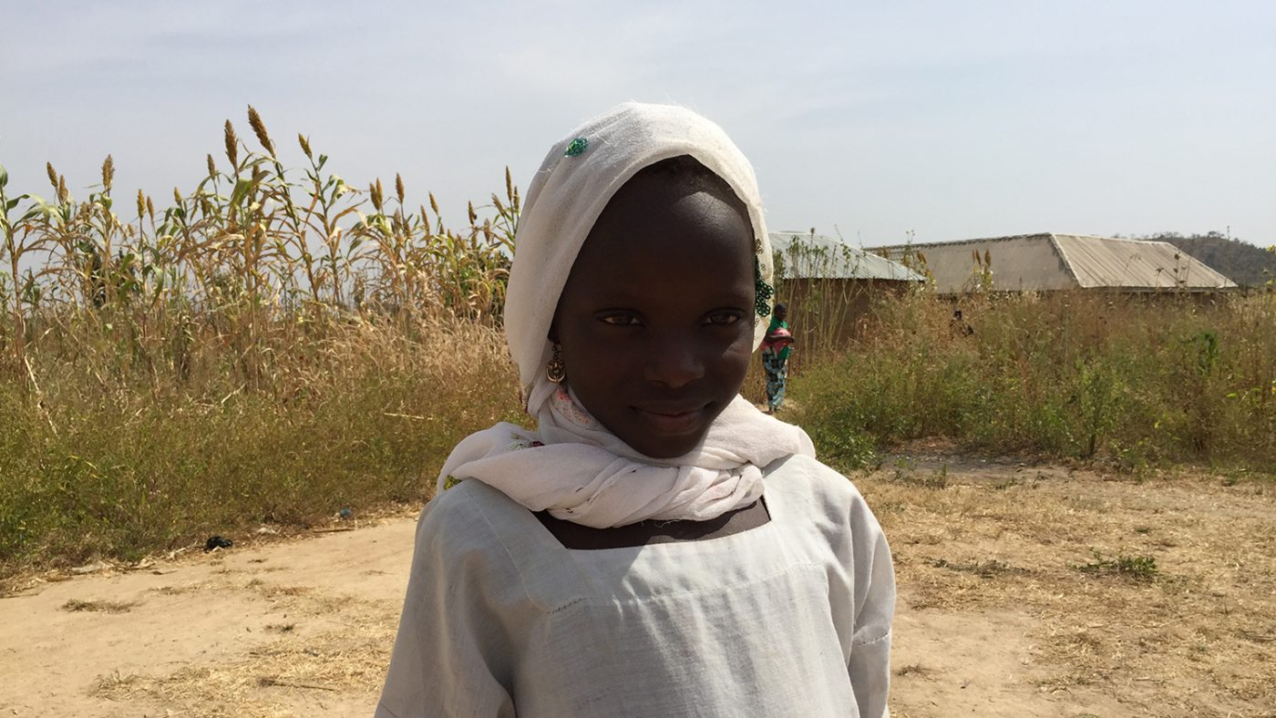 7 year old Dorcas is standing outside, smiling. She is the one billionth treatment beneficiary.