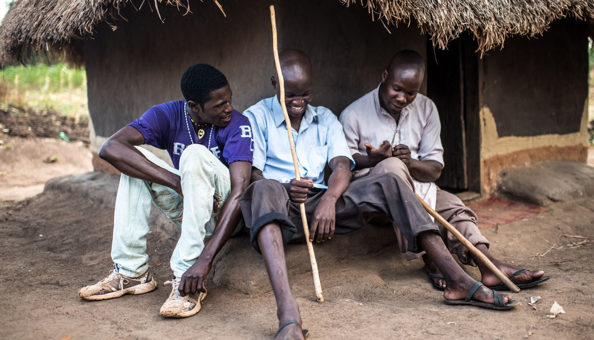 A man holding a cane, sitting outside a house with two friends and laughing.