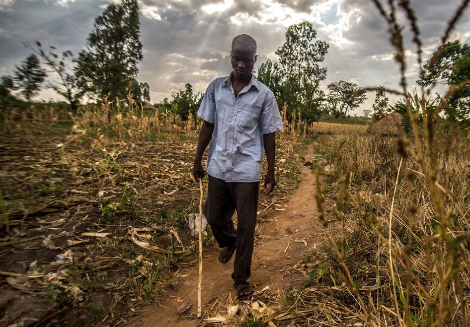 A man using a cane to help him walk along a dirt track in a field.