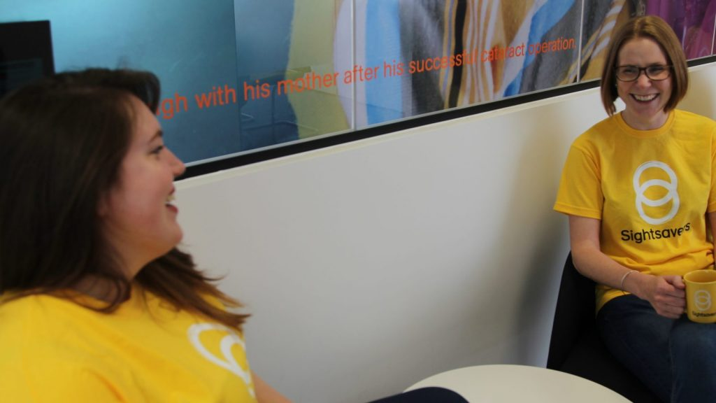Two ladies sitting down in yellow tshirts with the Sightsavers logo on them. Both ladies are laughing and looking at each other.