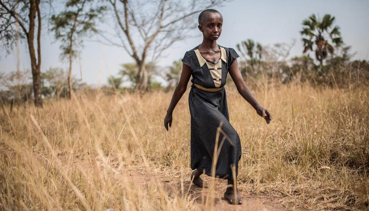 A woman walking carefully across a field of dry grass.