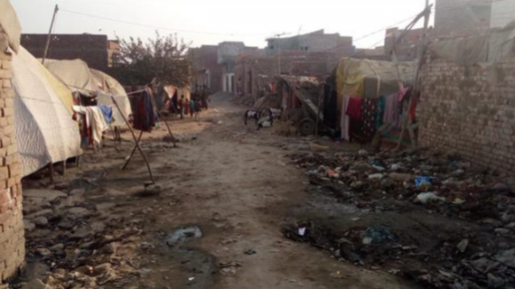 A street in an urban settlement with tents on either side of a wide dirt track.