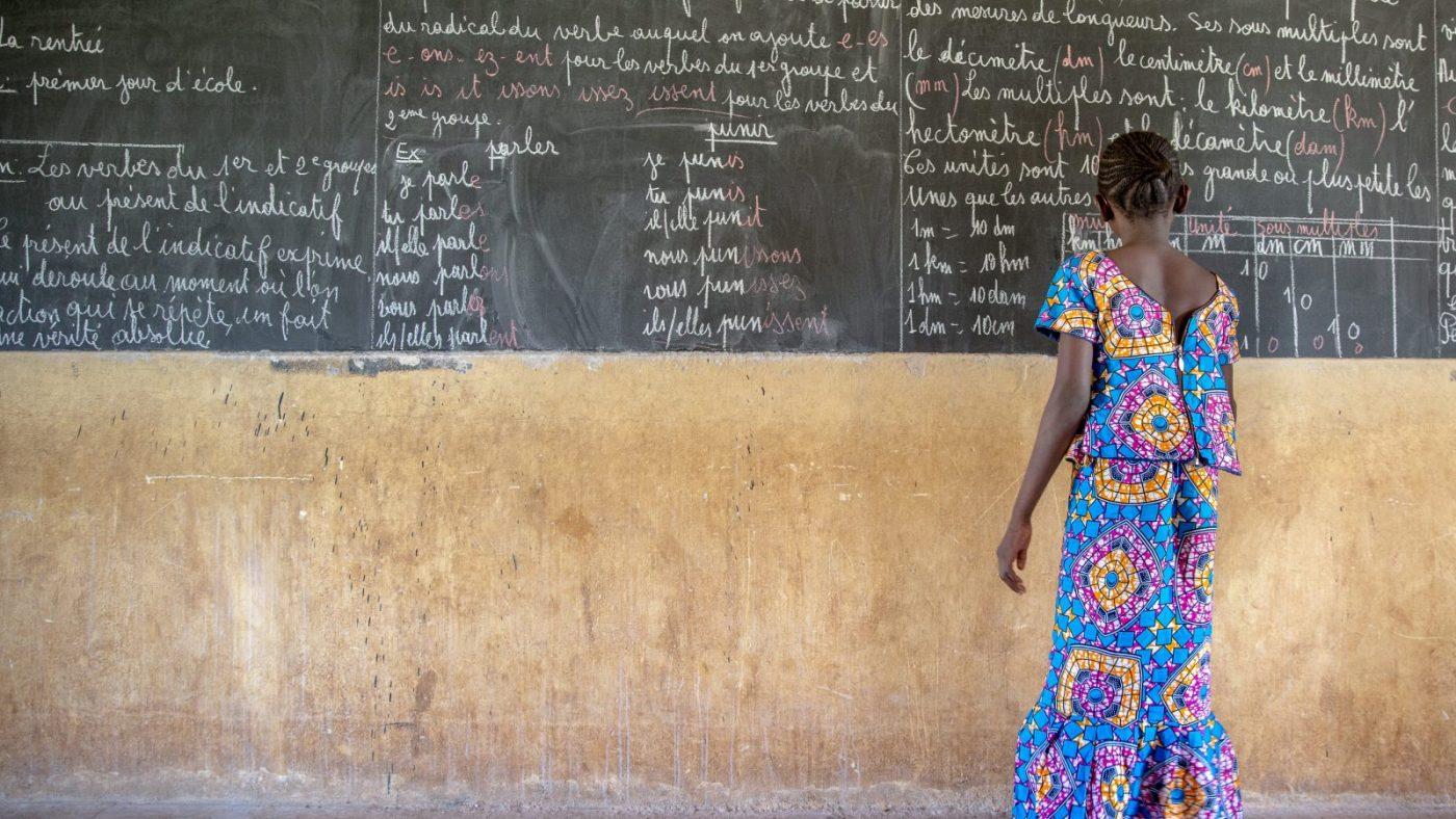 Mafoune writing on the blackboard in her classroom.