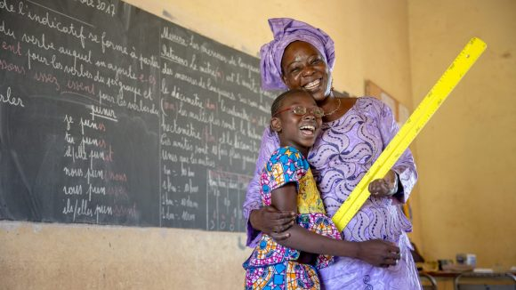 Mafoune and her teacher smiling and embracing in front of a classroom blackboard.