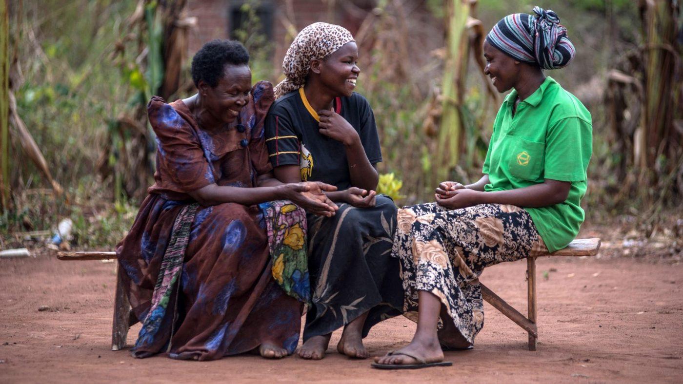 Three women sat outside talking.