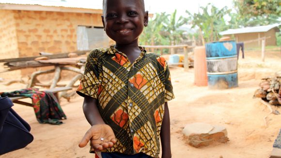 A young boy holds out his hand which has a pill in it. He is smiling and standing outside.