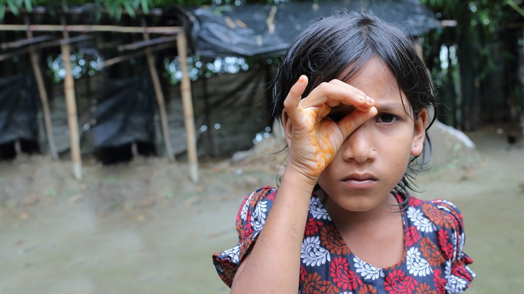 A young girl cups her hand around her eye, trying to see better.