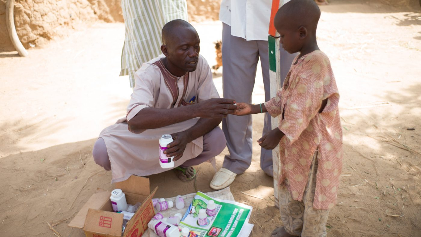 A community volunteer hands a tablet to treat NTDs to a young boy.