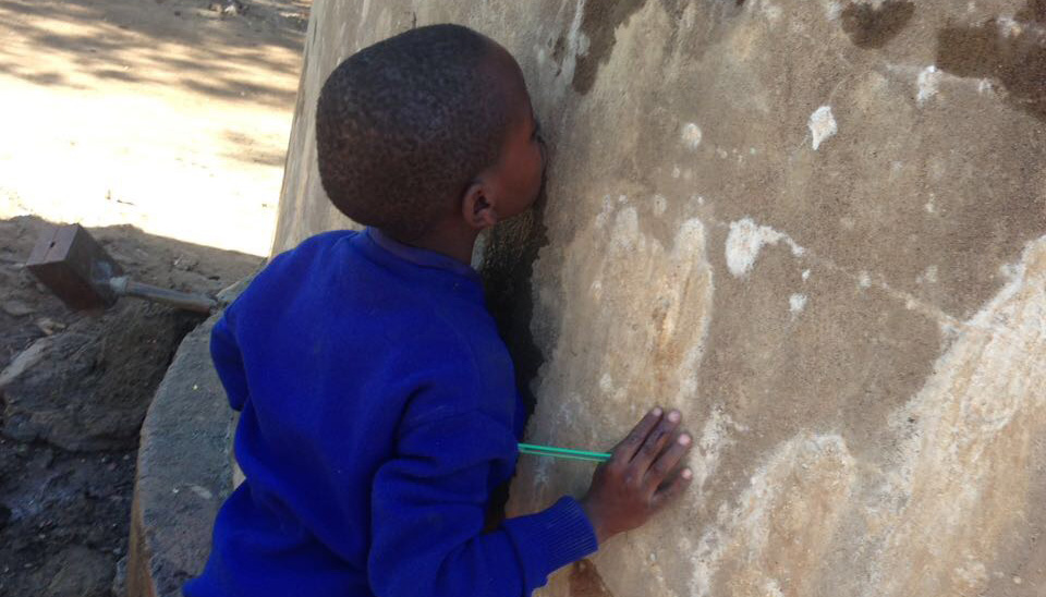 A young boy with his face pressed against a crack in a concrete water tank.