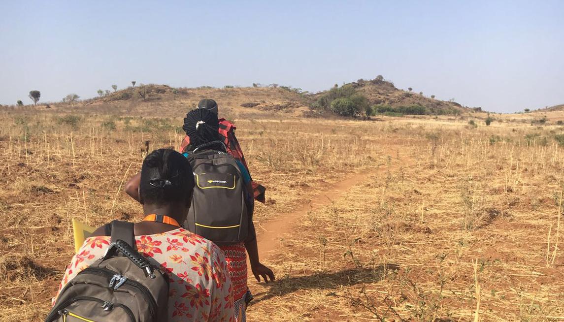 Three people walking across a flat, dry landscape.