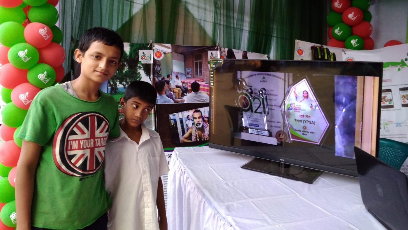 Two boys standing next to a stand.