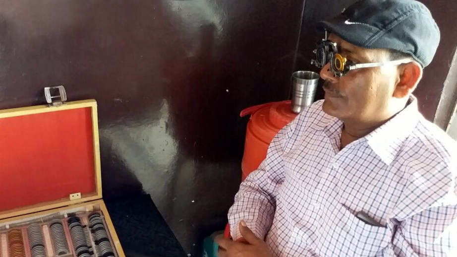 A trucker receives a detailed eye examination from an optometrist. He is sat down with a pair of examination glasses on.