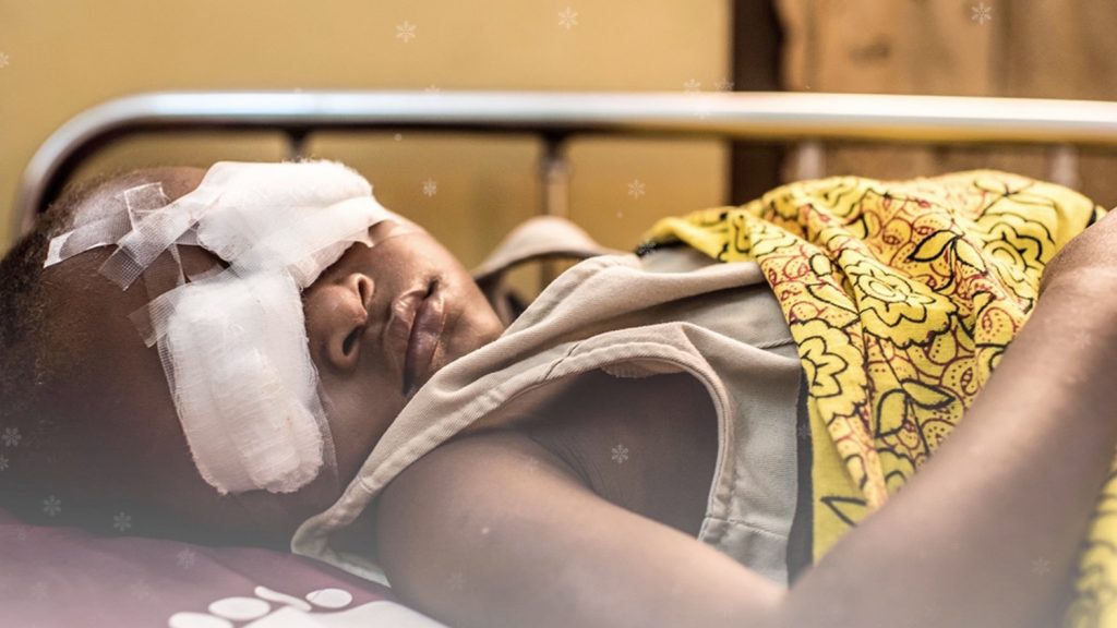 A young girl lays on a hospital bed with bandages over both her eyes.