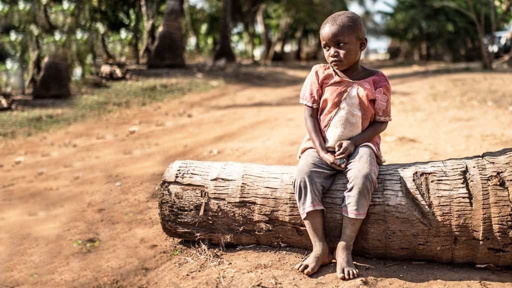 A young girl sits alone on a large tree stump.