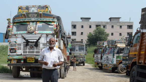 A man in India, wearing glasses, standing in front of a truck..