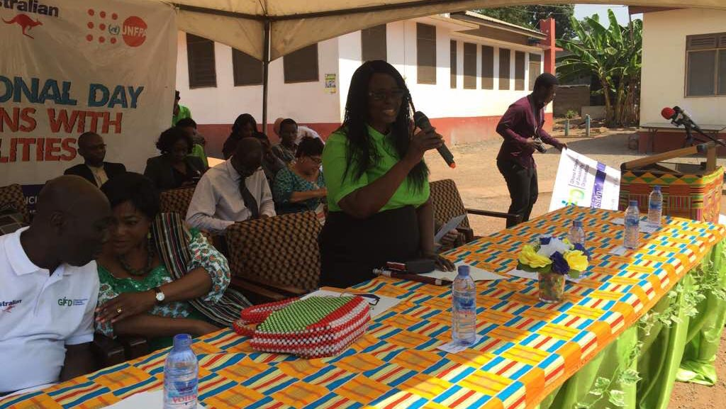 Gertrude Oforiwa Fefoame is speaking into a microphone. She is standing behind a table covered in a colorful tablecloth. To her right are two other people. There is a group of people sat behind them.