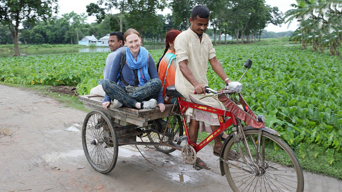 A group of people riding on an uncovered autorickshaw in Bangladesh.