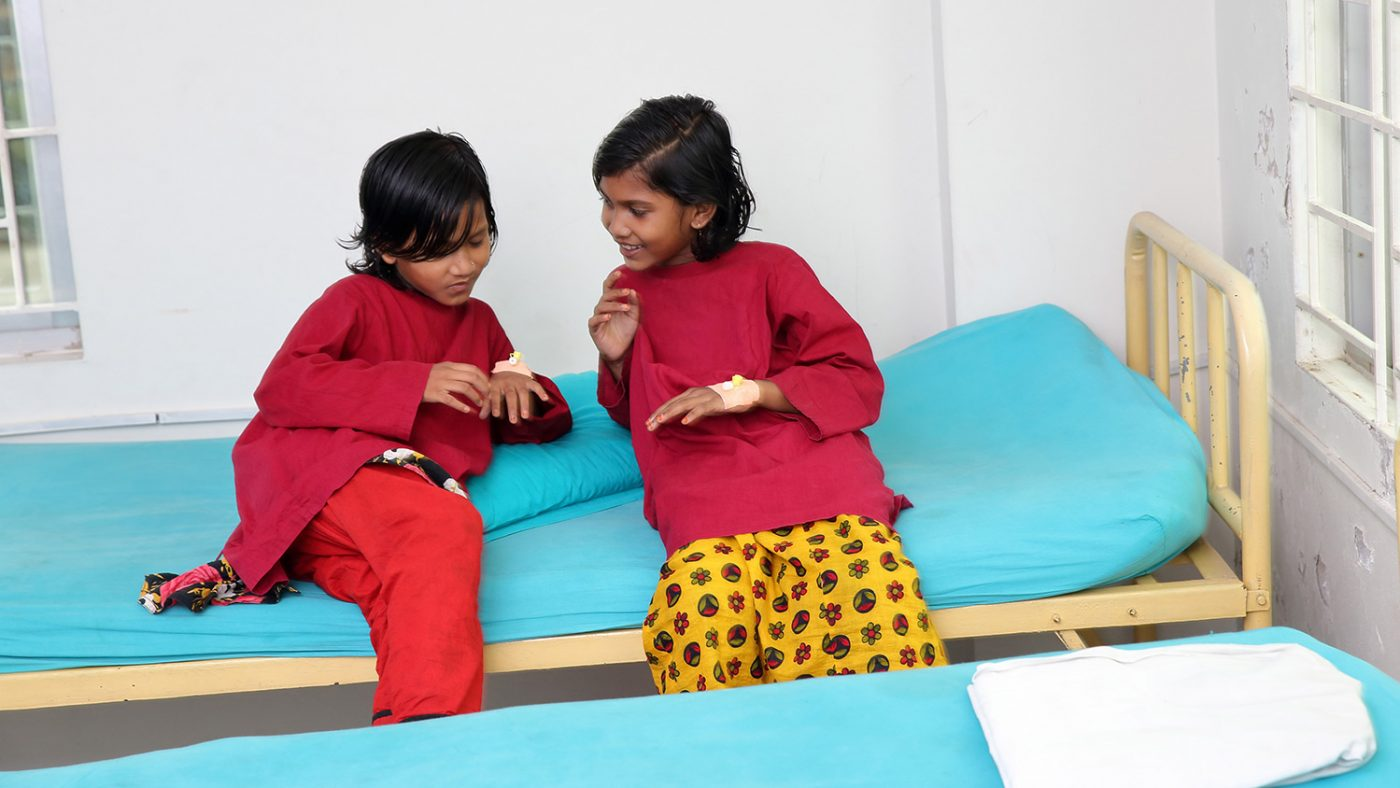 Suborna and Sumiya sits and chat on a hospital bed.
