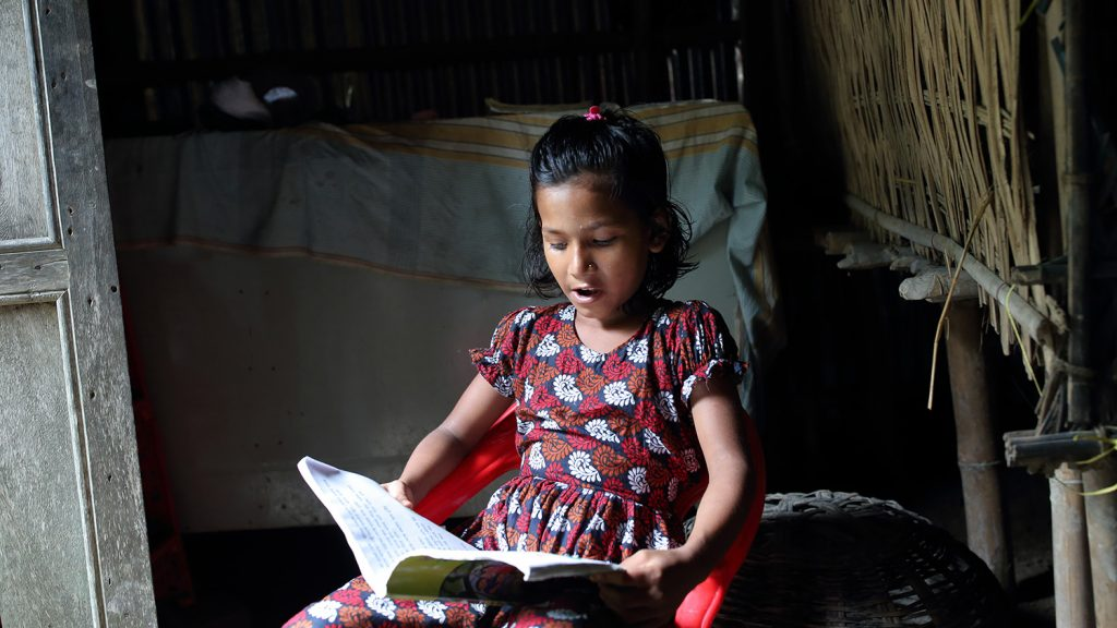 Suborna reads her book, without the aid of the hand.