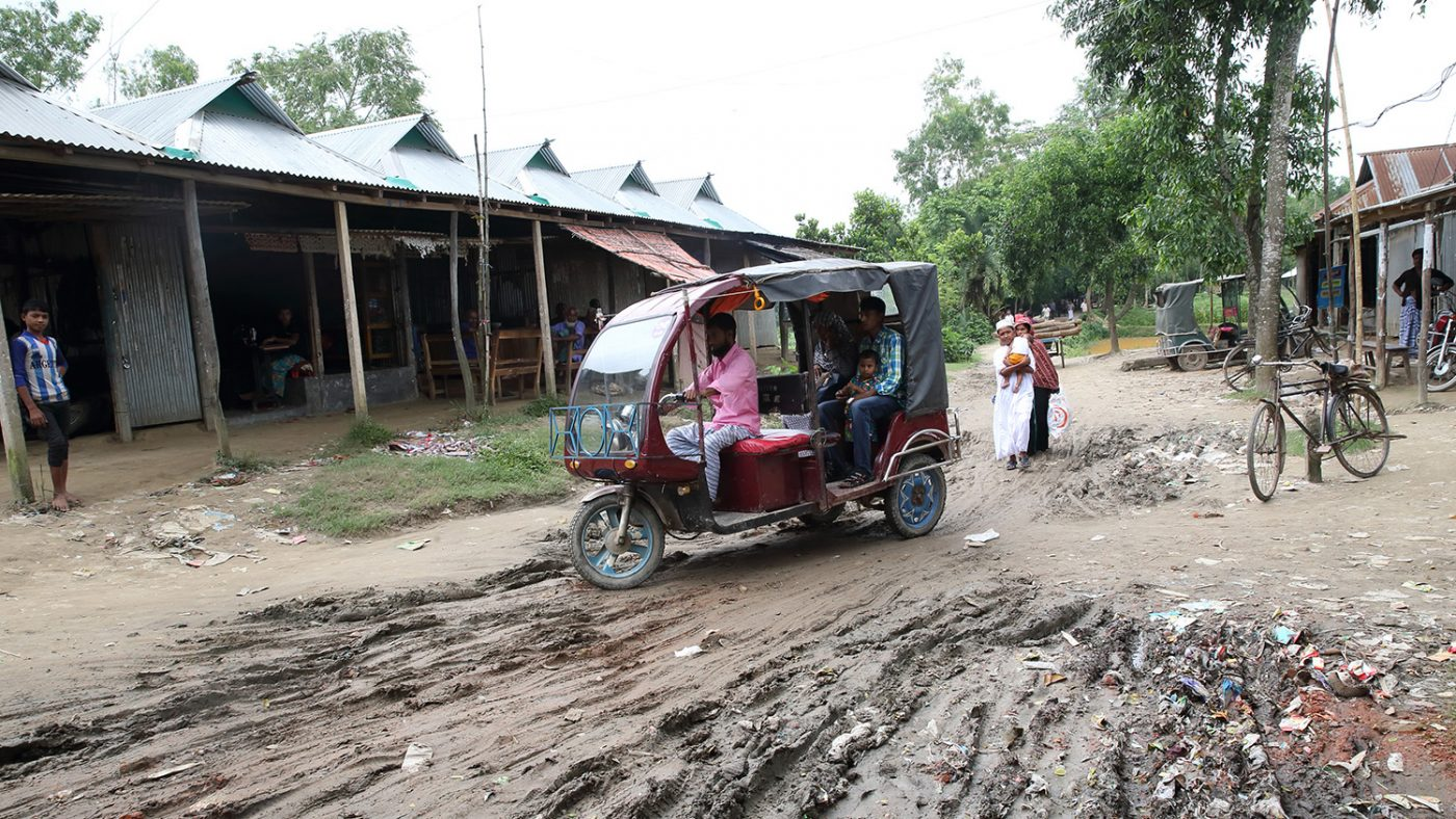 An image of an autorickshaw navigating through some thick mud.