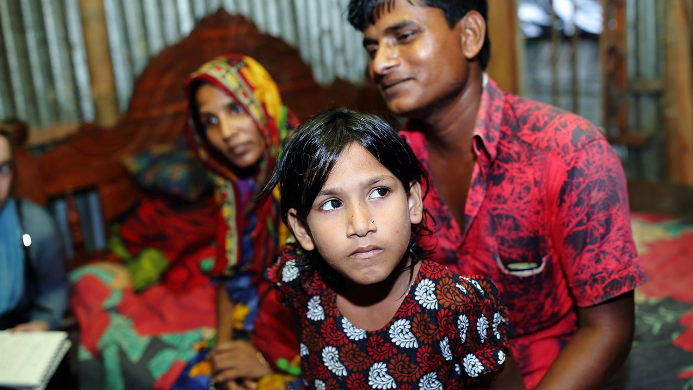 Suborna sits inside her home with her parents.
