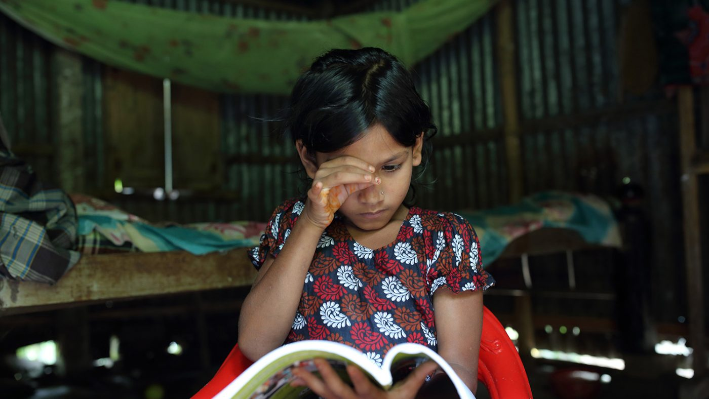 Suborna attempts to focus on a page of a book by cupping her hand around her eye.