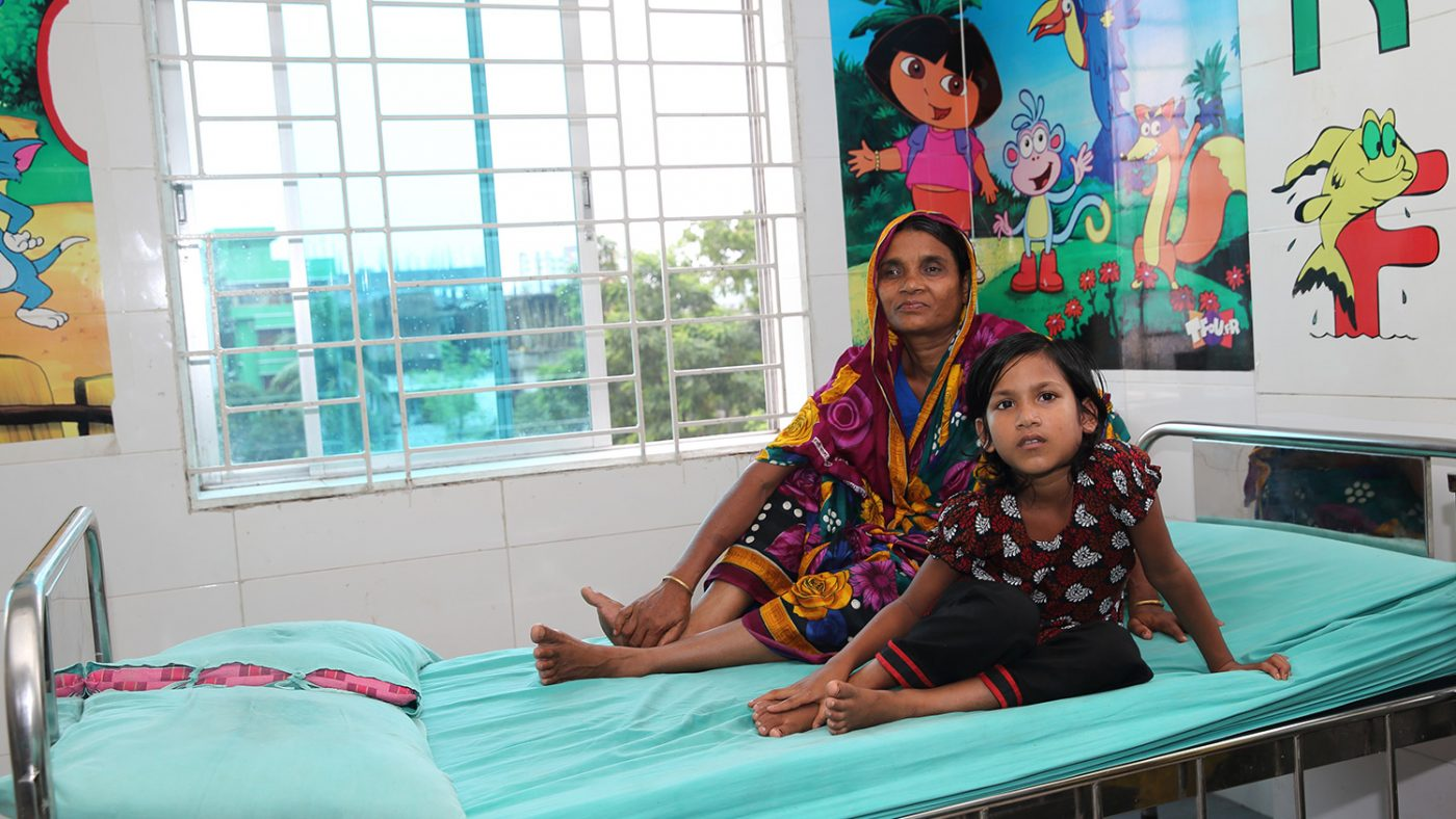 Suborna sits with her mother on a hospital bed.
