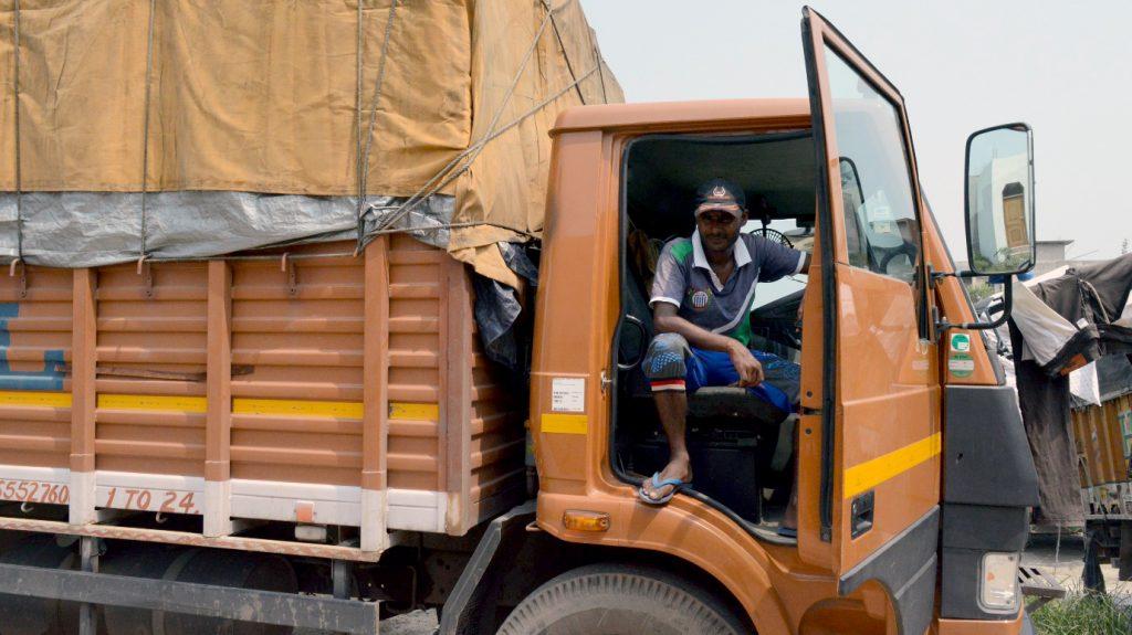 Mohammad Islam Ansari sitting in his orange truck looking out of the door.