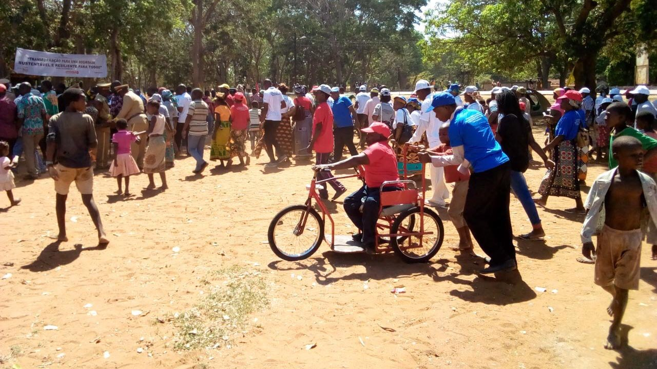 A group of people at a fair. A man on a red mobility vehicle is being pushed along by a grown man and a younger boy.