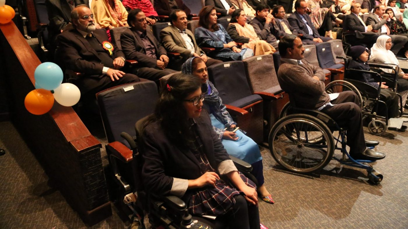 A group of people (audience) watching a stage. There are two people at the front who are sat in wheelchairs.