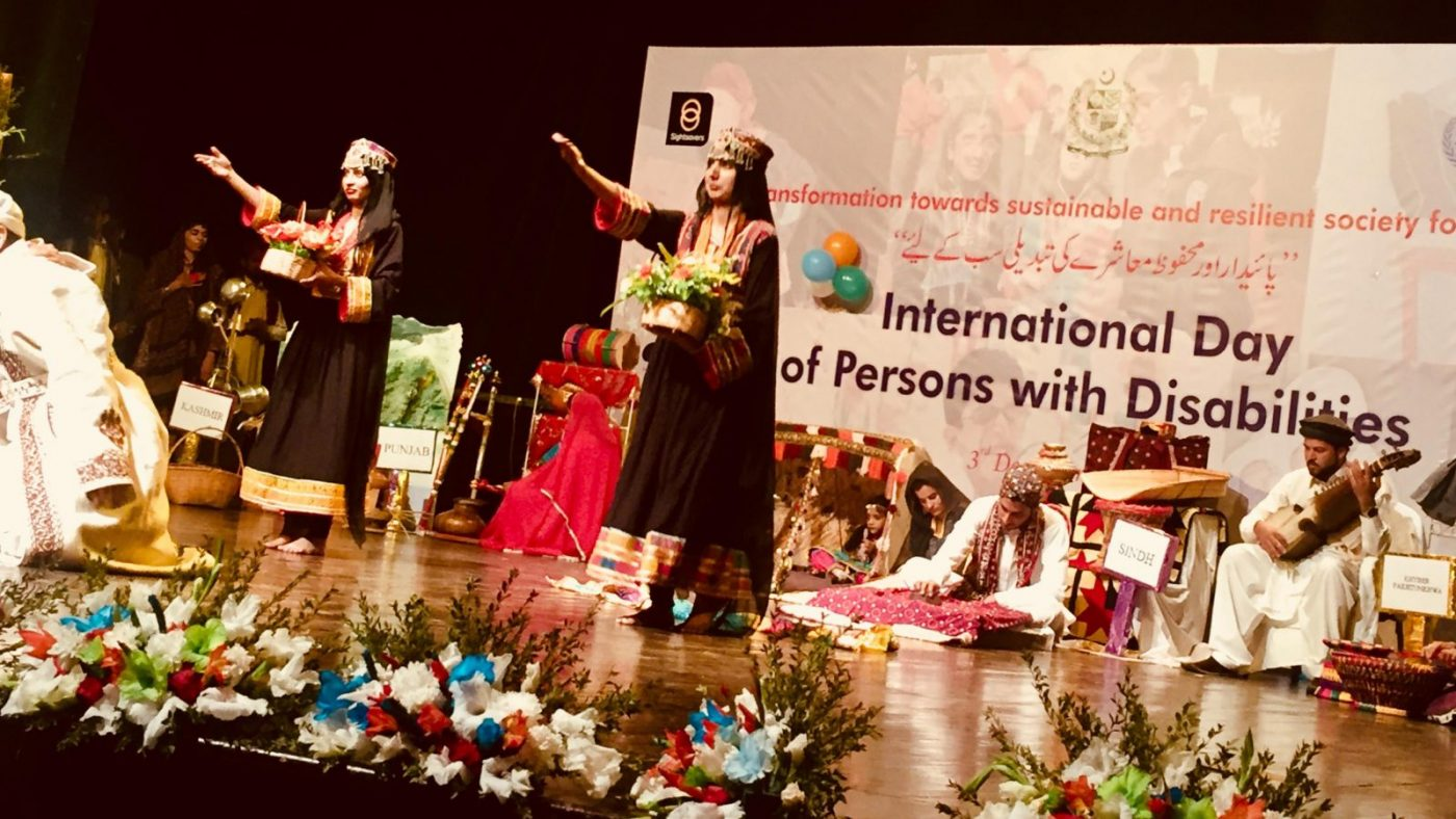 Two girls are doing a performance on a stage. There is a lot of flowers at the front of the stage.
