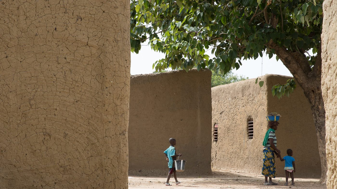 People walking through two mud buildings in the village where Sayon lives in Mali.