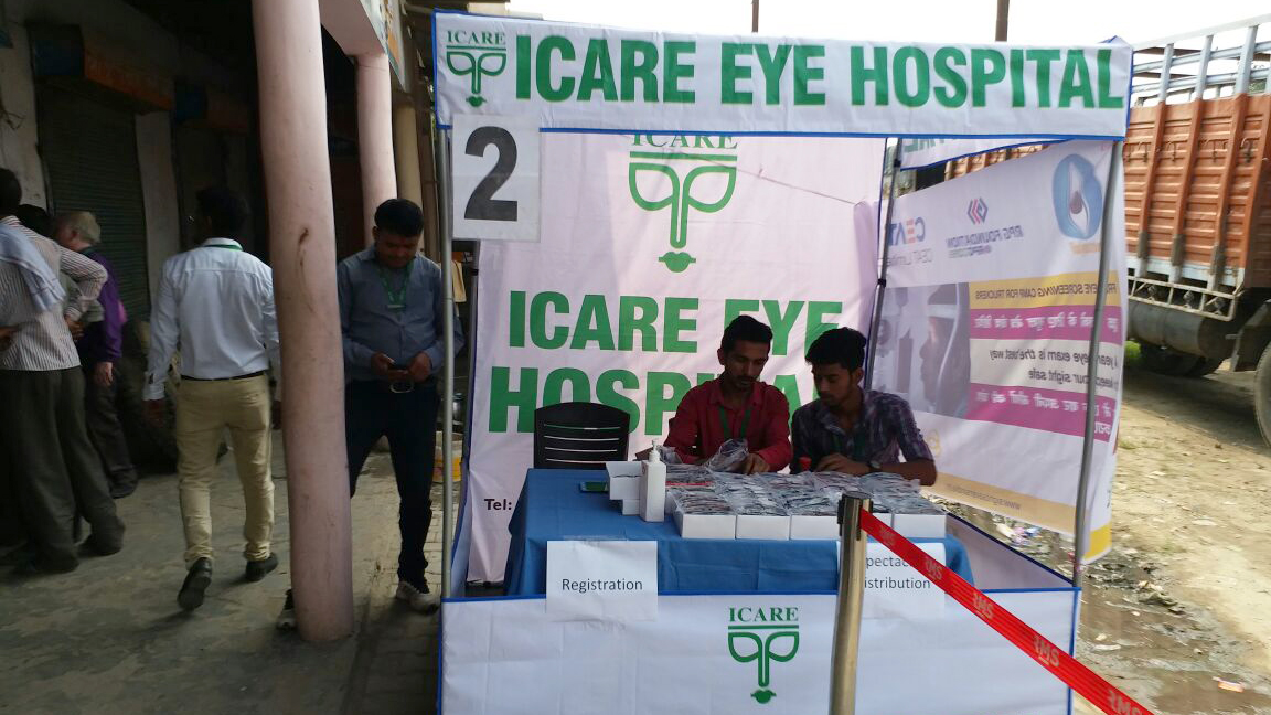 Two men site at a registration desk at an eye health camp.