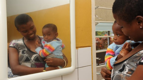 A young girl and her mother look into a mirror.
