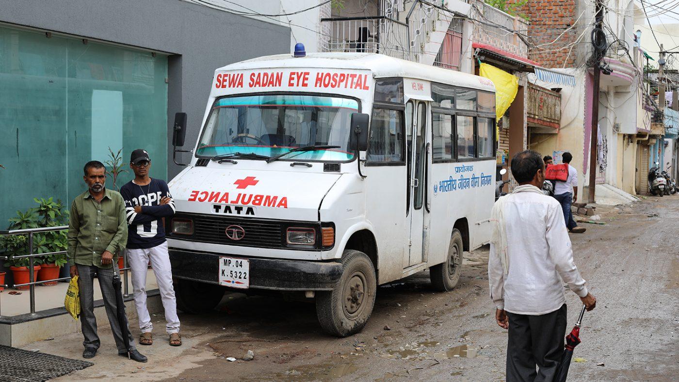 A bus from the Sewa Sadan Hospital sits on a muddy road in Bhopal.