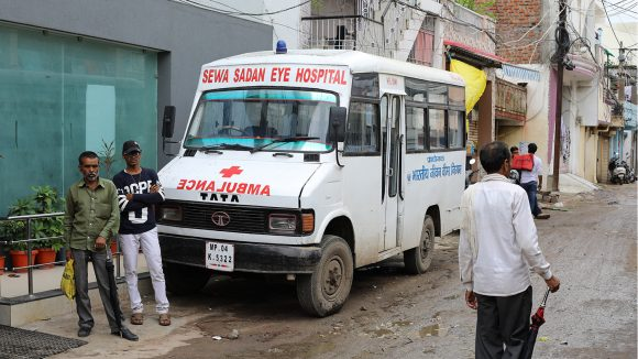 A bus from the Sewa Sadan Hospital sits on a muddy road in Bhopal.