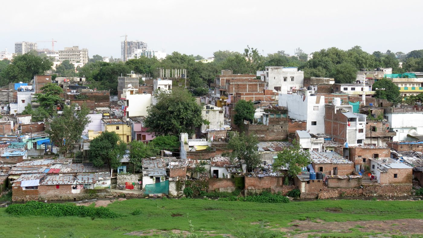 A view of Bhopal's slum areas, featuring small shack-like huts and plenty of greenery.