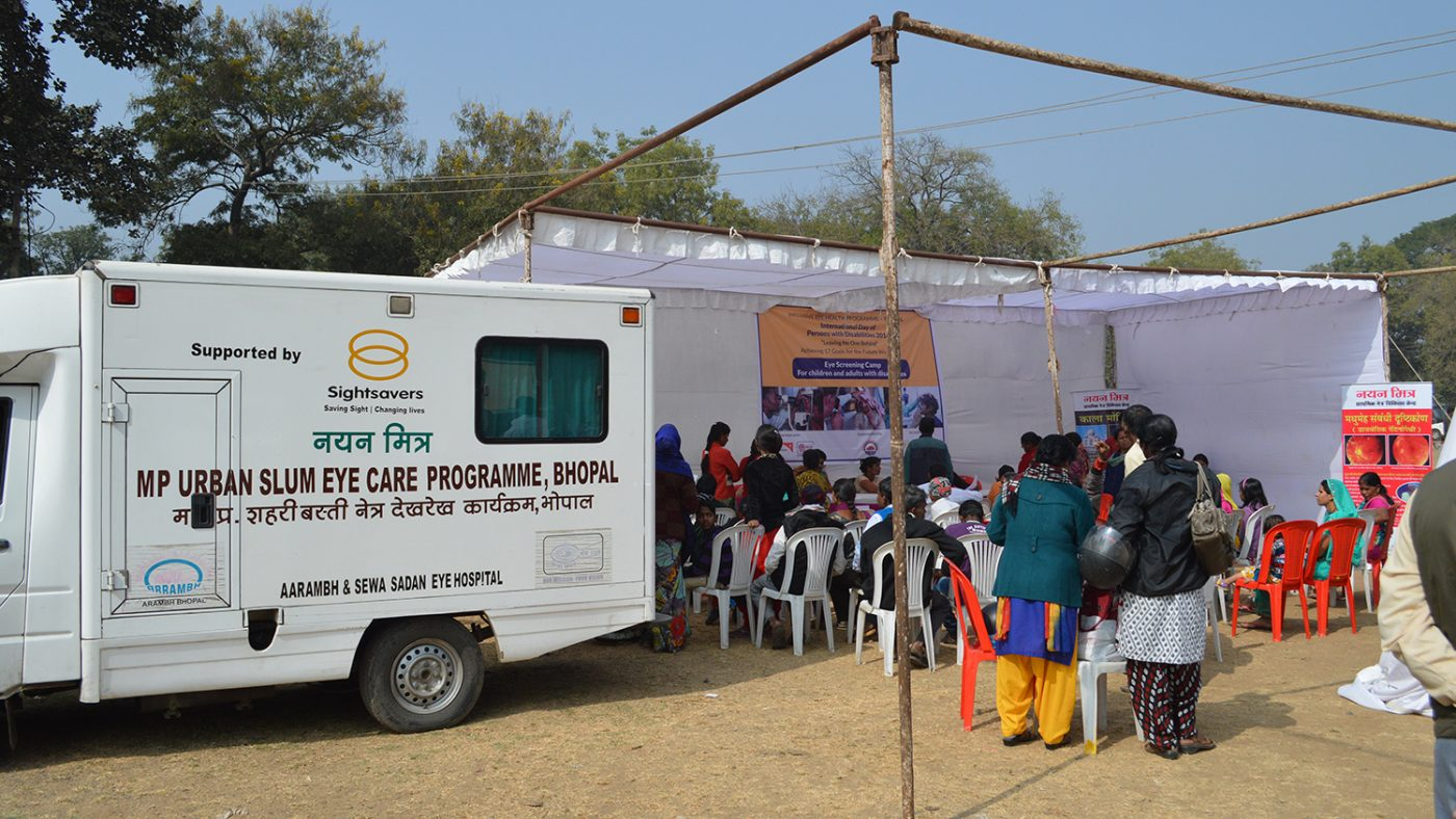 A vision outreach camp in Bhopal, with chairs set up next to a van featuring the words 'Urban slum eye care programme'.