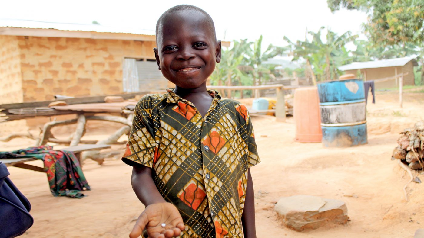 Young boy Evans Anim smiles as he holds out his Mectizan medication, which he will take to protect him against river blindness.