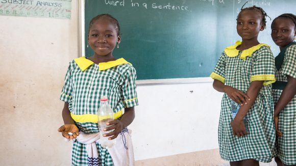 A schoolgirl holds a tablet in her hand and smiles.