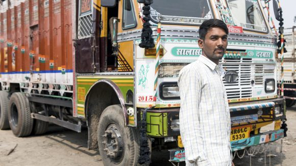 Sandeep Kumar, a truck driver from India, stands in front of his truck.