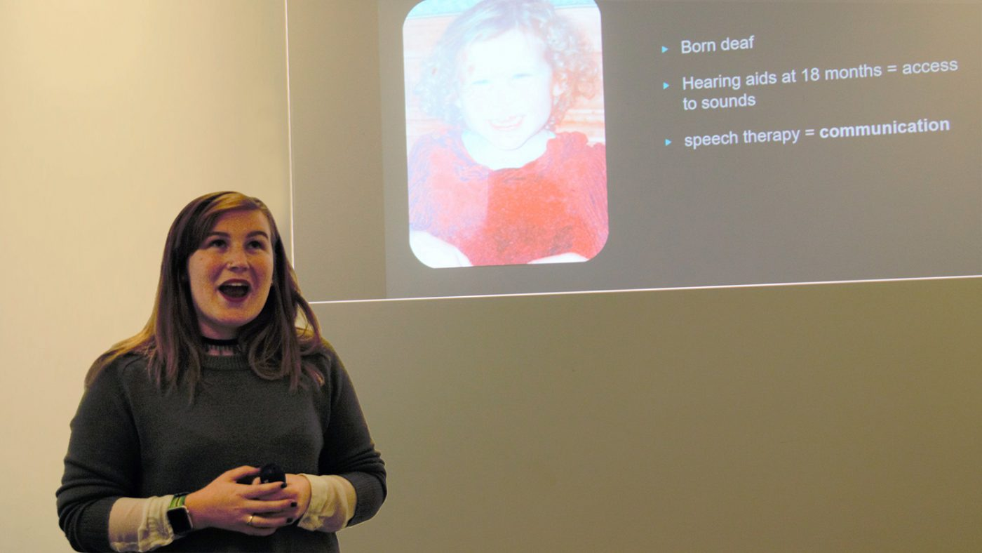 Molly Watt stands in front of the projector during her presentation at Sightsavers.