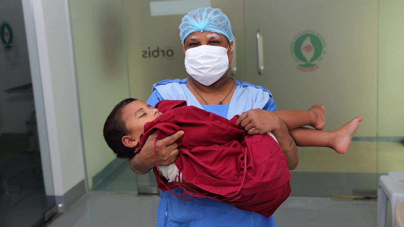 Nadir is carried into theatre by a surgical nurse.