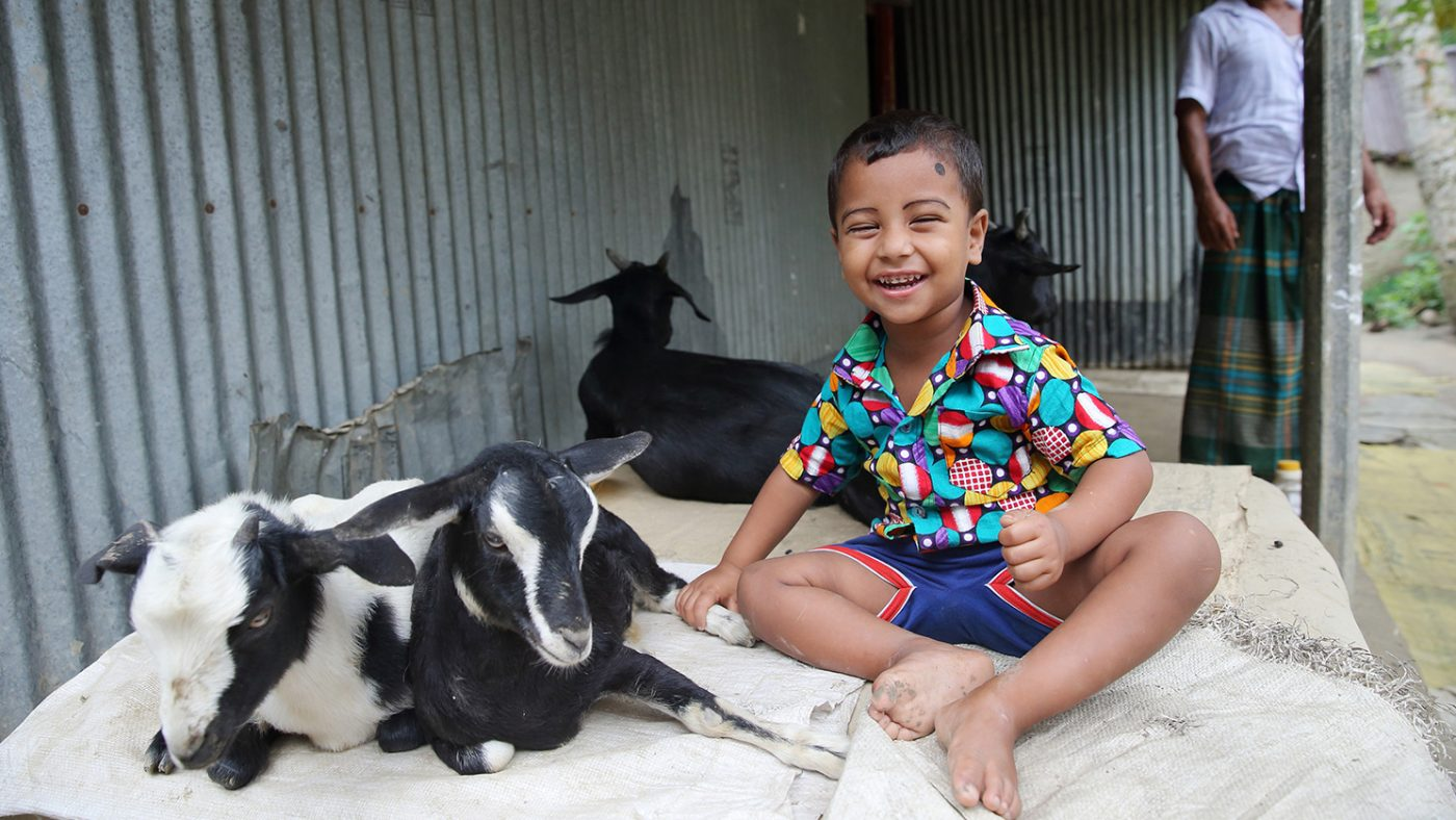 Nadir smiles while sitting next to the family's goats.