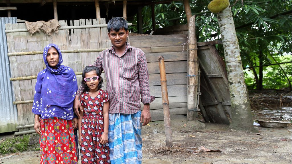 Suborna stands with her mother and father outside her home in Bangladesh.