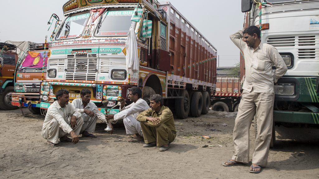 Indian truck drivers sit on the ground and relax in front of their trucks.
