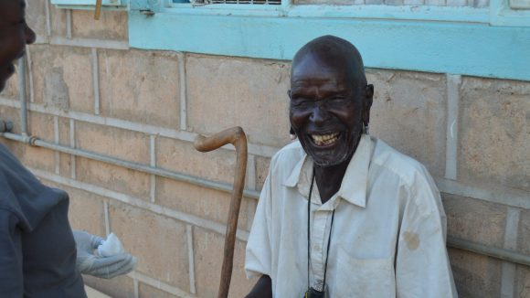 A man sitting outside with a huge smile.