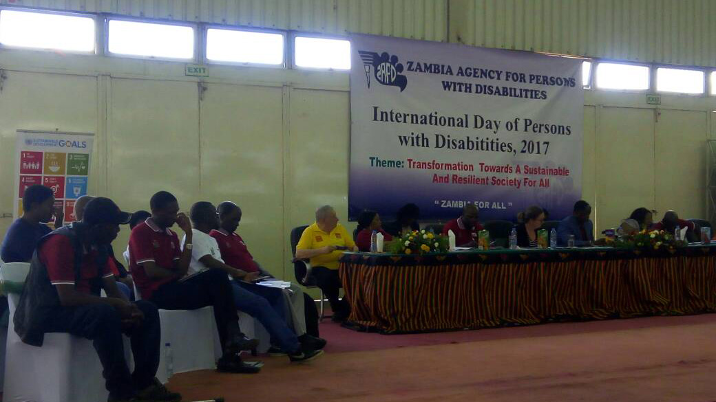 A group of people sit at a long table on a stage. A banner hangs behind them saying 'Zambia agency for persons with disabilities, International Day of Persons with Disabilities 2017. Theme: Transformation towards a sustainable and resilient society for all.'