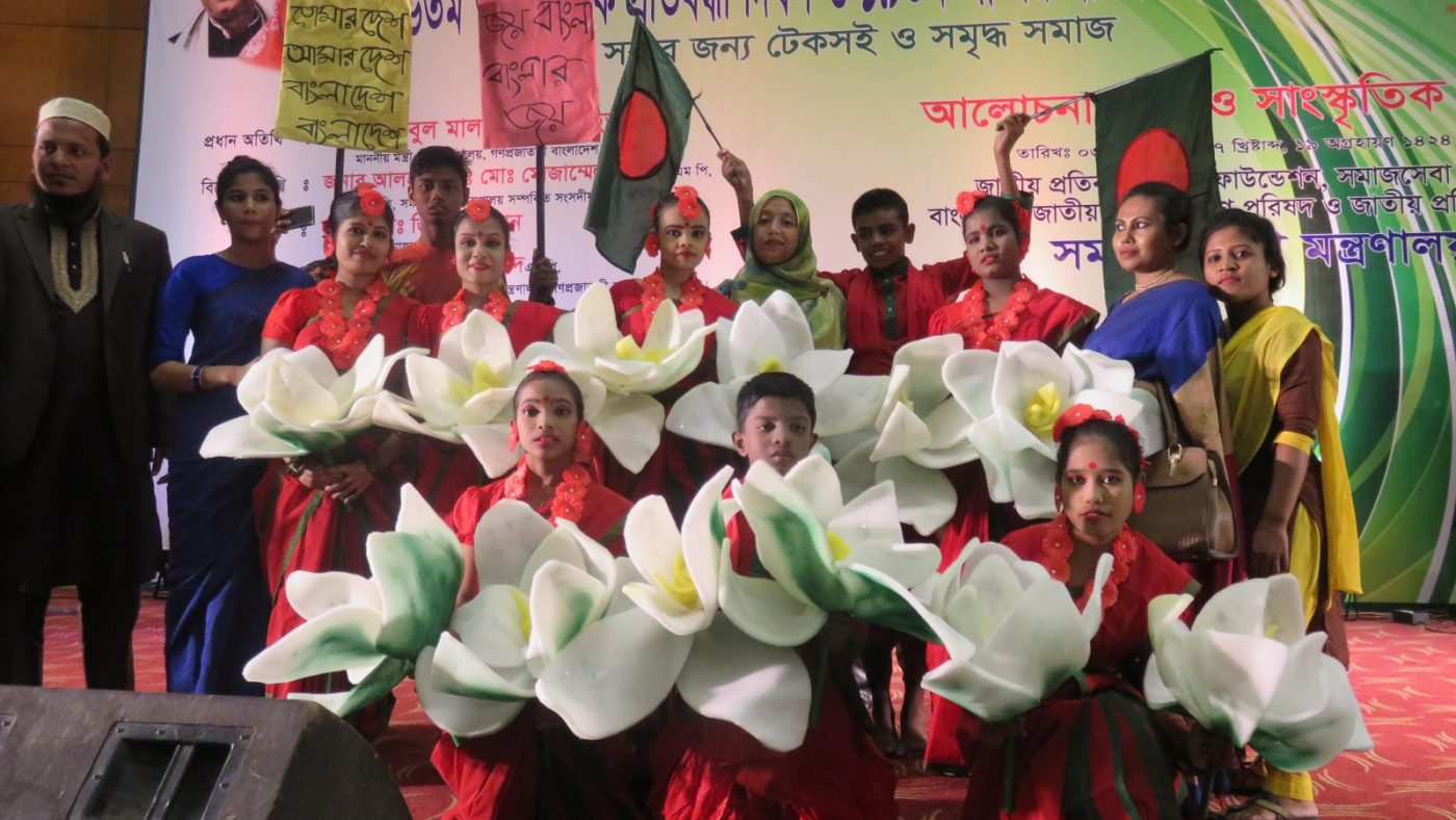 A group of performers dressed in red holding huge white artificial flowers and flags.