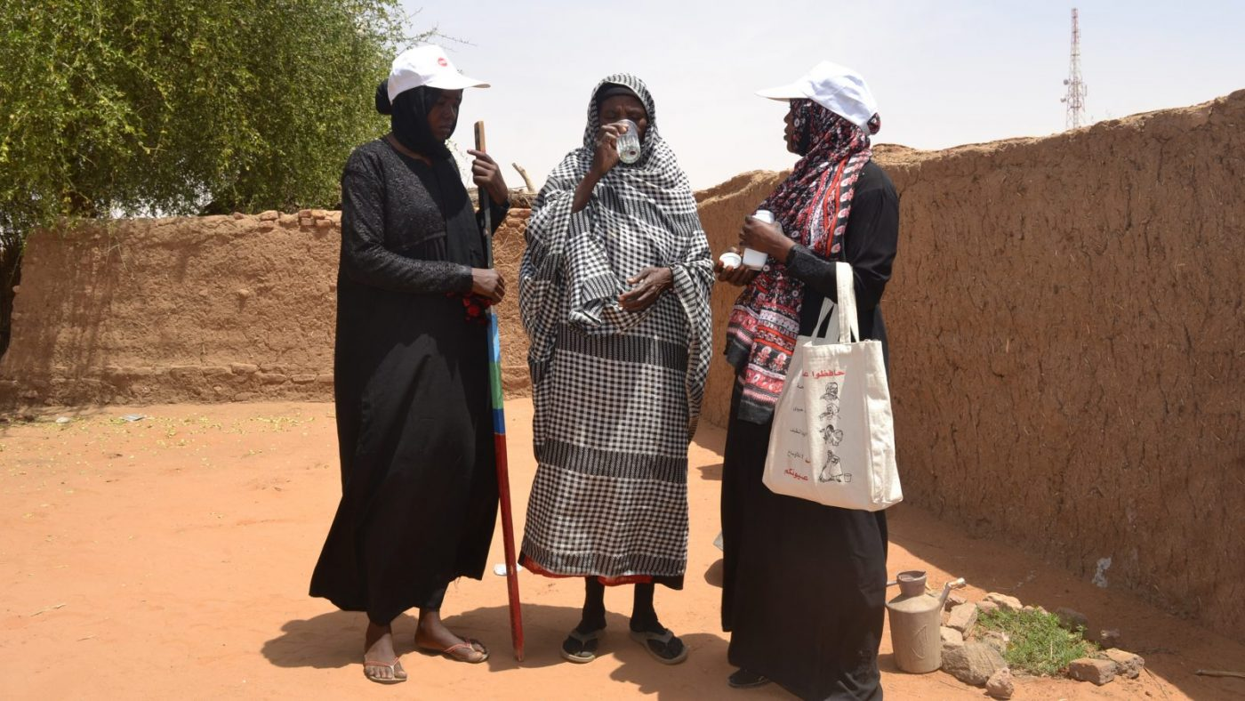A woman receives treatment for trachoma from two community volunteers.